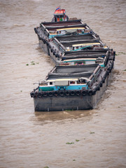 A barge, a flat-bottomed ship,for carry sand  in Chaopraya river drag by tugboat.