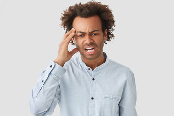 Stressful young African American male keeps hand on temple, looks desperately down, has headache, curly hair, frowns face in discontent, dressed in elegant shirt, isolated over white background