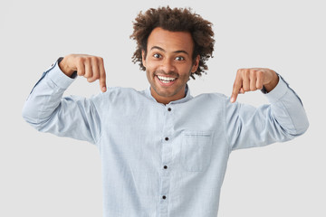Happy mixed race curly young male with toothy smile, curly hair, points down, says that there is something wonderful downstairs, has friendly facial expression, poses against white background.