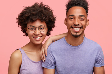 Horizontal shot of happy African American woman and man have truthful relationships, toothy smile, happy to meet with friends, dressed casually, isolated over pink background. Emotions concept