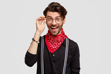 Happy male hipster being glad to meet with friends with common interests, wears spectacles and stylish clothes, has joyful expression, stands alone against white background. People and style
