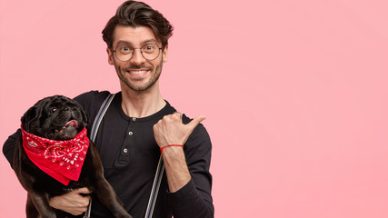 Young hipster male with positive expression, trendy hairstyle, holds pedigree dog with red bandana, points at copy space aside, pose together against pink background. People and animals concept