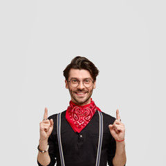 Vertical shot of happy bearded male with happy expression points upwards, wears black shirt with red bandana, has friendly smile, trendy haircut, isolated over white background with copy space above
