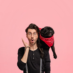 Human emotions concept. Emotive stupefied young male hipster has trendy haircut, keeps mouth round, carries favourite black dog, notice something surprising during walk, stands against pink wall
