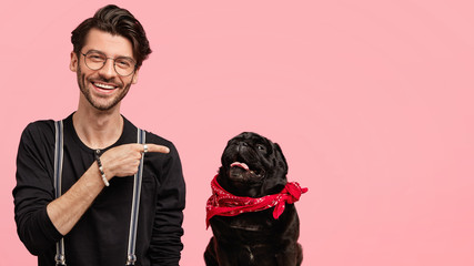 Studio shot of happy Caucasian male has bristle, points at his favourite dog, expresses care and love to animals, walk together in park, have good relationships, isolated over pink wall, blank space