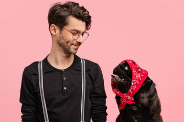 Affectionate male dog owner looks with pleased expression and love at his funny pet with bandana on head, feels responsibility, play together at home, isolated over pink background. Pedigree puppy