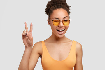 Joyful black female with crisp hair, dark skin, makes peace sign, blinks eye, has positive expression, wears yellow shades, poses against white background. Cool African American woman gestures