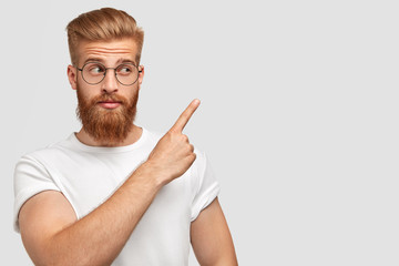 Horizontal shot of attractive Caucasian male has ginger hair and beard, points with fore finger aside, dressed in t shirt in one colour with background, shows blank space for your advertisement Wall mural