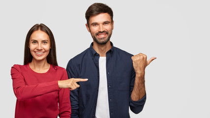 Cheerful brunette young female in red sweater with healthy skin, positive bearded guy stand together in studio, point aside at blank space, show place for your advertisement or promotional text