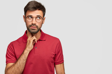Pensive dreamy male with European appearance looks thoughtfully upwards, thinks about something, analyzes life situation, wears red t shirt, stands against white background with free blank space