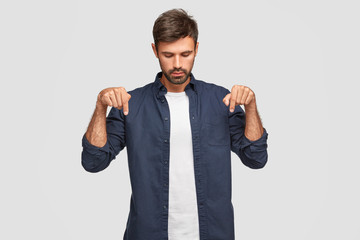 Concentrated serious young European male with appealing appearance focused down, indicates with both index fingers, has beard and mustache, wears elegant shirt, isolated over white studio wall
