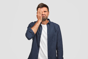 Displeased unshaven male has bothered face, covers eye with hand, feels bored, frowns, dressed in dark blue fashionable shirt, stands against white background. People and facial expressions.