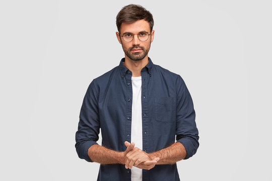Waist up portrait of handsome serious unshaven male keeps hands together, dressed in dark blue shirt, has talk with interlocutor, stands against white background. Self confident man freelancer