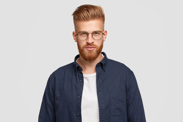 Indoor shot of serious redhead youngster has thick ginger beard, mustache, looks confidently at camera, wears fashionable shirt, has specific appearance, isolated over white studio backround