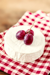 Cheese camembert on wooden desk, top view. Soft creamy cheese Brie with red grape