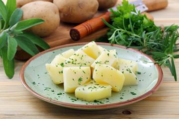 patate bollite con spezie e verdure su sfondo tavolo di cucina