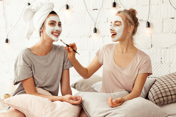 Portrait of attractive happy girls having fun sitting in bed with pillows. Cheerful women wearing facial cosmetic mask for soft smooth silk skin. Beauty skincare concept