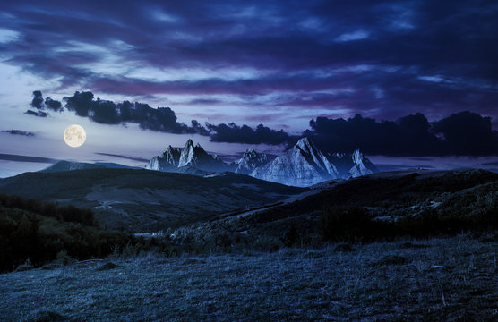 composite of countryside at night in full moon light. gorgeous cloudscape over the mountains with rocky peaks.
