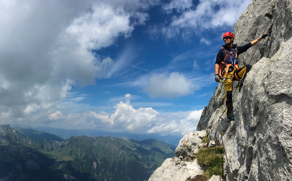 Young man climbing on a rock in Swiss Alps - via ferrata/klettersteig