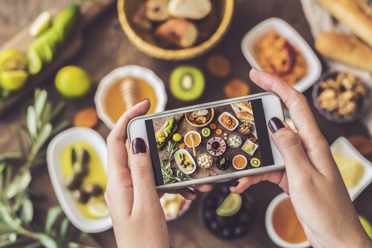 Woman taking a photo of breakfast table