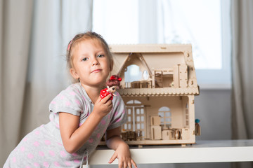 a girl playing with a dollhouse