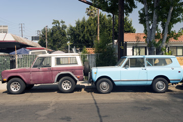 A view of two vintage suv truck cars in the street in Venice, California