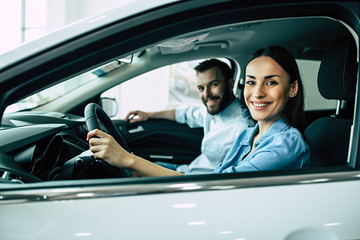 Happy beautiful young couple chooses and buying a new car for the family in the dealership while sitting inside one of car. Wall mural
