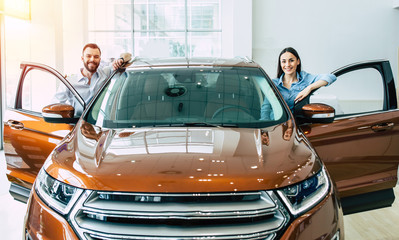 New comfortable SUV. Happy young lovely couple in casual wear buying first new family car together in dealership.