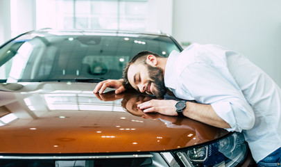 Dreams come true today. Happy handsome bearded man buying a car in dealership