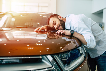 Happy handsome bearded man buying a car in dealership, guy hugging hood of new car