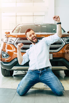 Happy owner of a new car. Emotional handsome man in casual clothes is happy standing on the knees when buying a car in the dealership.