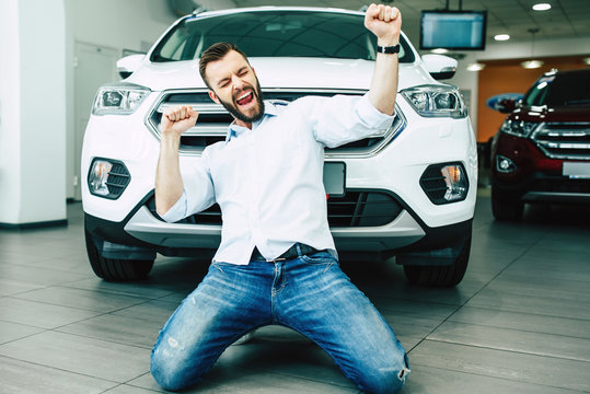 Happy handsome man buying a new white car in dealership and dancing on the floor against the auto.