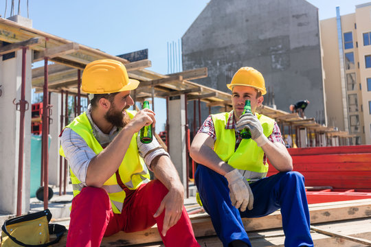 Two young workers smiling while drinking a cold alcoholic or non-alcoholic beer, during break at work on the construction site in a sunny day of summer