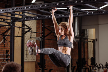 close up side viow blonde strong woman is hanging on the horizontal bar. cross fit , health care concept