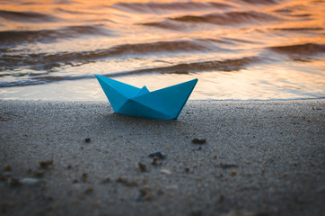 Paper blue ship is thrown on sandy shore of lake at sunset.