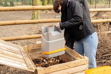 Woman empty organic wastes in wooden compost heap