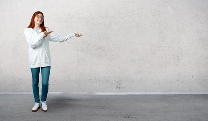 Young redhead girl in an urban white sweatshirt with glasses presenting and inviting to come and standing on a vintage gray wall