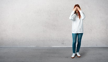 Young redhead girl in an urban white sweatshirt with glasses covering eyes by hands. Do not want to see something and standing on a vintage gray wall