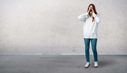 Young redhead girl in an urban white sweatshirt with glasses shouting with mouth wide open to the lateral and announcing something and standing on a vintage gray wall