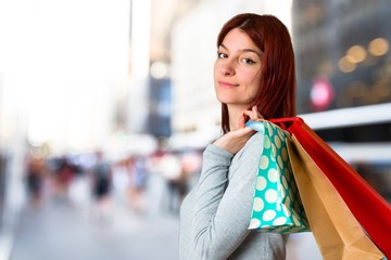 Young redhead girl holding a lot of shopping bags on unfocused background
