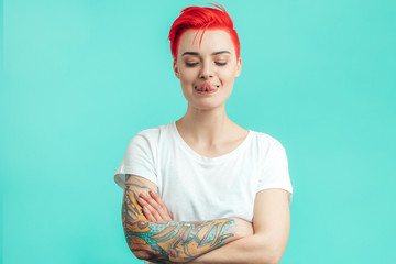 funny stylish girl trying to touch her nose with tongue. isolated blue background. copy space