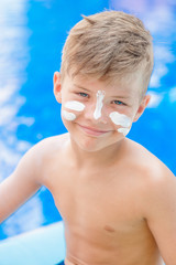 Protect sunscreen applied to the face of smiling young boy.  Summer vacation concept
