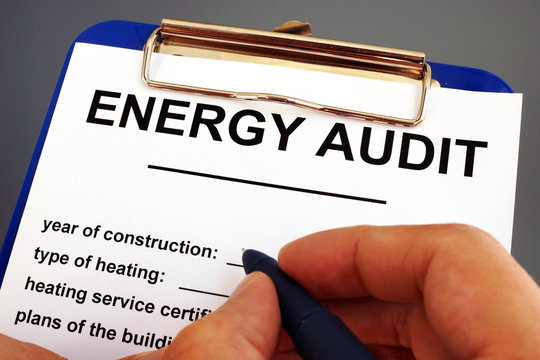 Man filling in energy audit form in a clipboard.