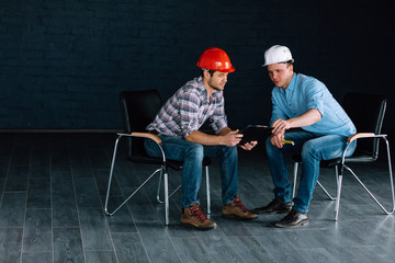 two co-workers in hardhats are checking the list of necessary materials for construction. copy space