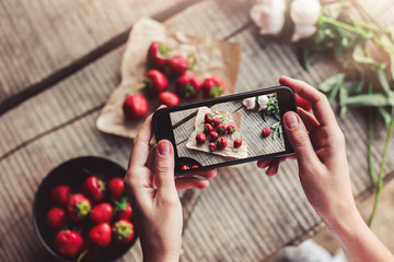 Girl's hands taking photo of breakfast with strawberries by smartphone. Healthy breakfast, Clean eating, vegan food concept