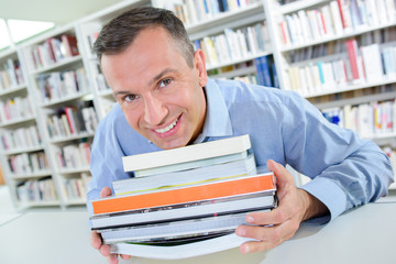 Smiling man holding stack of books