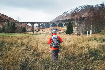 Man traveler walks neaar famous Glenfinnan viadukt in Scotland