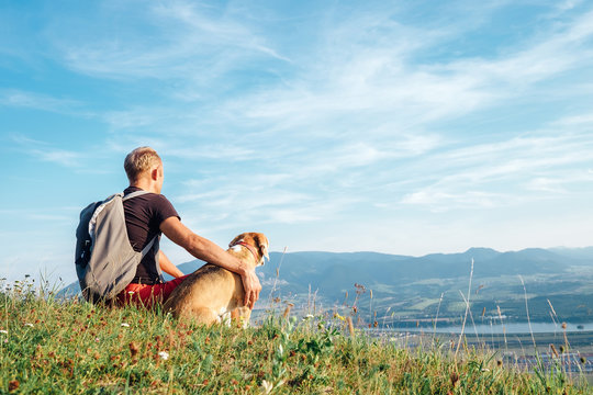 Man with his beagle dog sits on the top of hill over the mountain valley