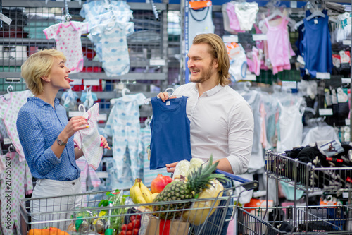 3b6f733a9d Attracrive couple choose babywear at the kids apparel store in shopping  centre, buying clothes together