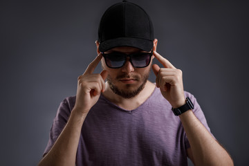 young bearded man in cap and sunglasses